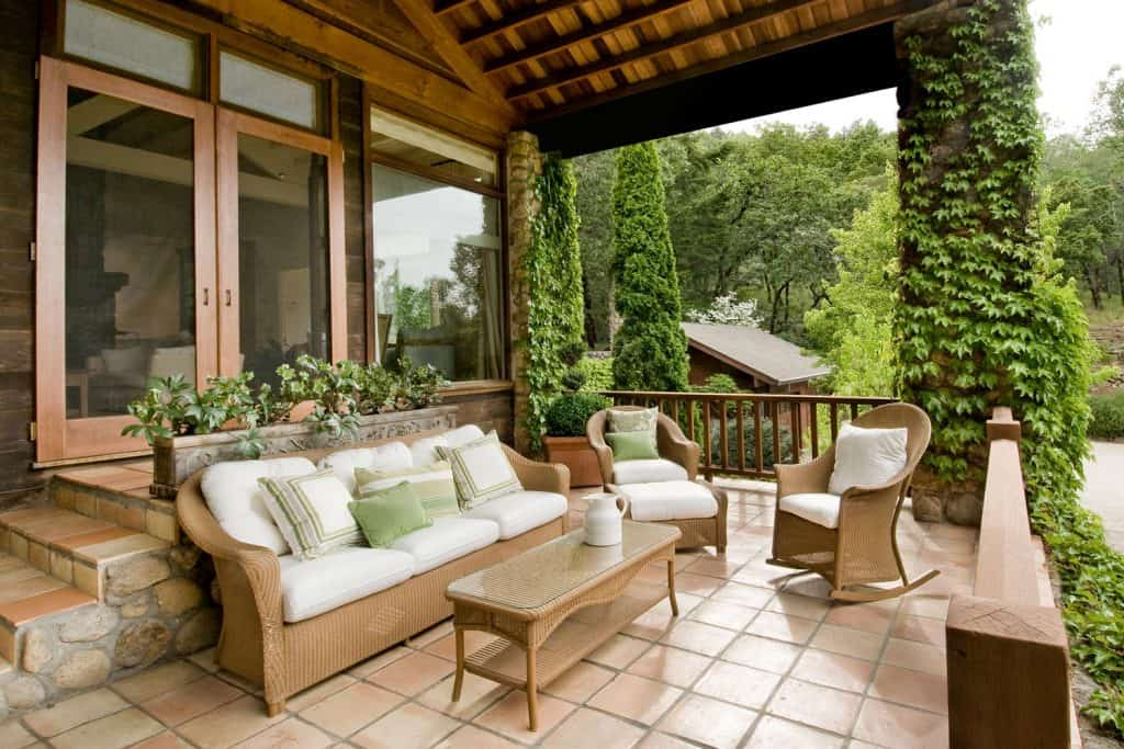 A front porch of a country home with rattan chairs incorporated with white chairs and throw pillows blending the cold and natural environment