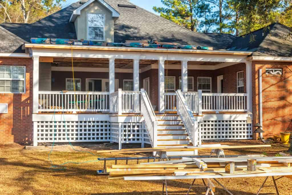 A gorgeous country home with a forest with deck skirting on the front porch and asphalt shingle roofing
