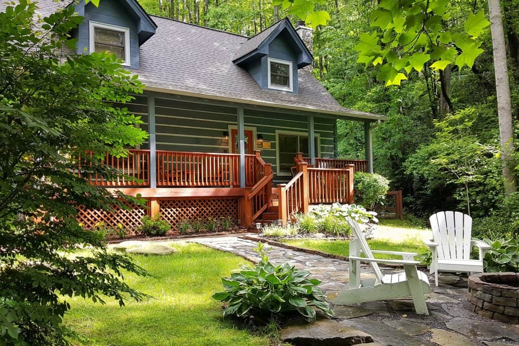A gorgeous country home with a country design and deck skirting on the patio with modern landscaping