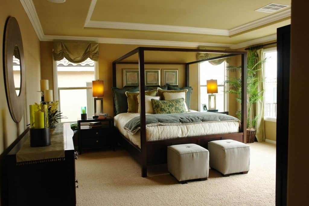 A gorgeous dark themed bedroom with green painted walls, a wooden rustic bed, and green colored tray ceiling