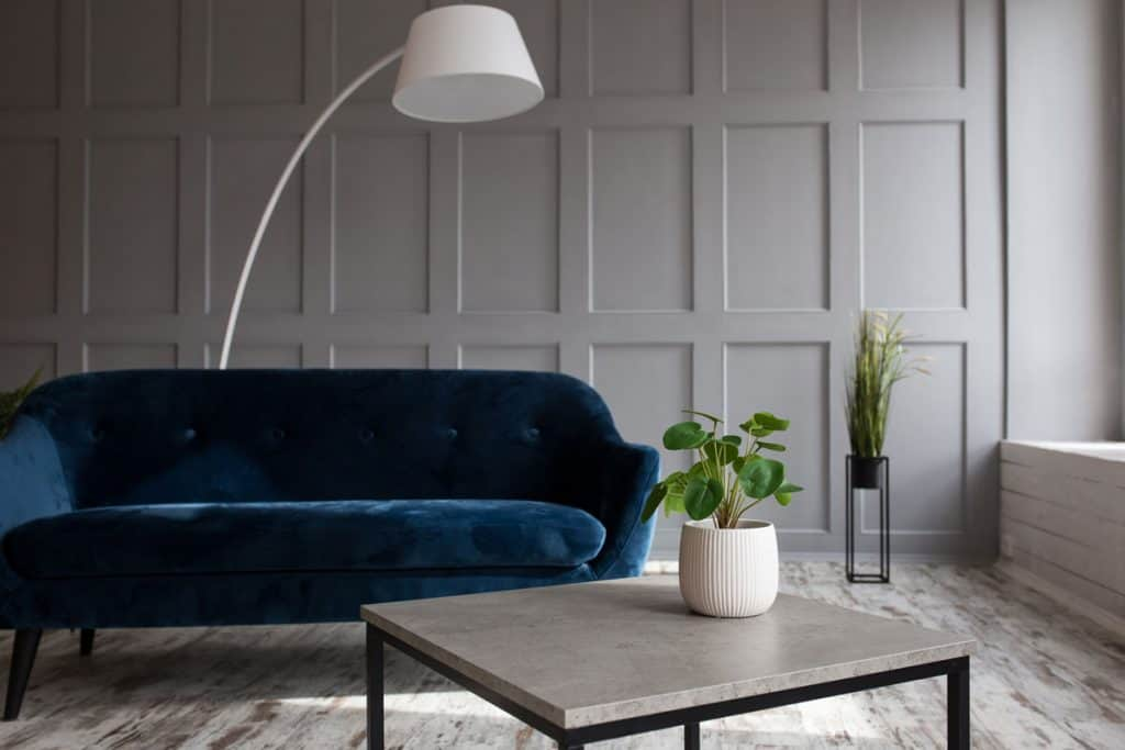 A gorgeous interior of a gray interior living room with a blue sofa and an arched white floor lamp