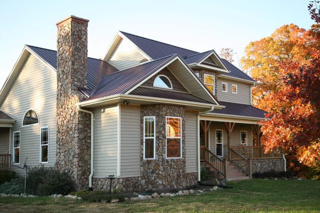 A gorgeous two storey country home with deck skirting and light gray painted wooden sidings