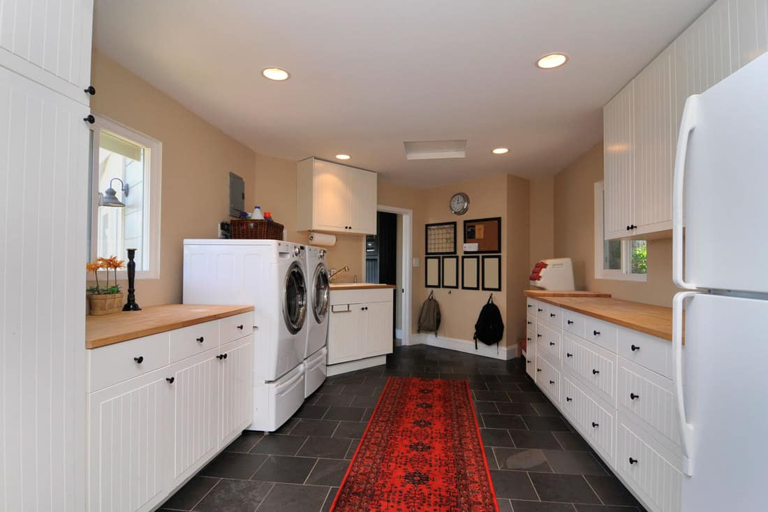 A home laundry room with red carpet and dark flooring, 15 Laundry Room Tile Ideas [Including For The Floor, Wall And Backsplash]