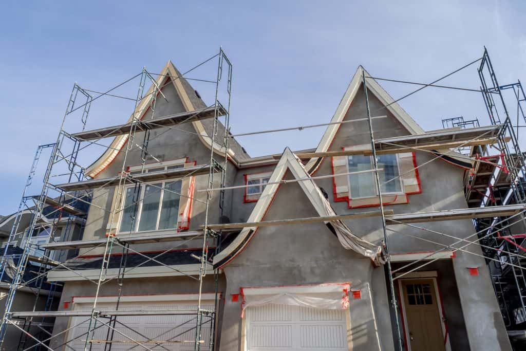 A house under construction with scaffoldings installed outside ready for Stucco application