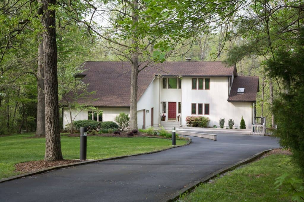 A huge forest mansion surrounded with tall trees and a house with white painted exterior walls and an asphalt driveway