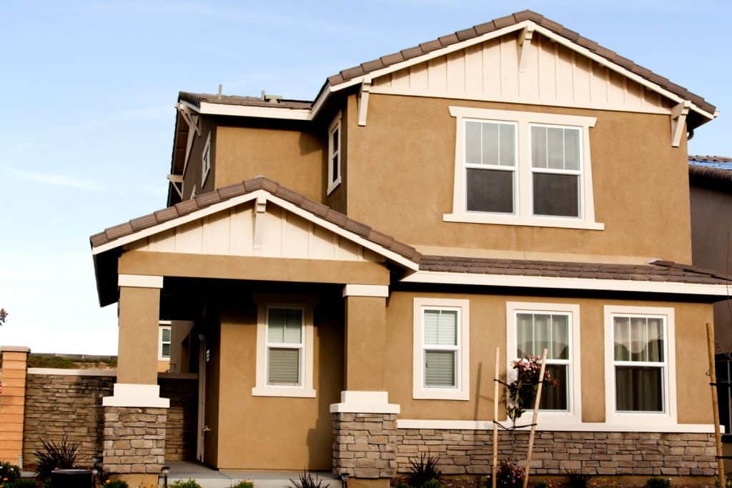 A huge house with a luxurious Stucco wall application, Can You Stucco Over Brick?