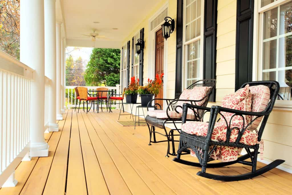 A huge wooden inspired porch with a rocking and wooden chairs with pillows