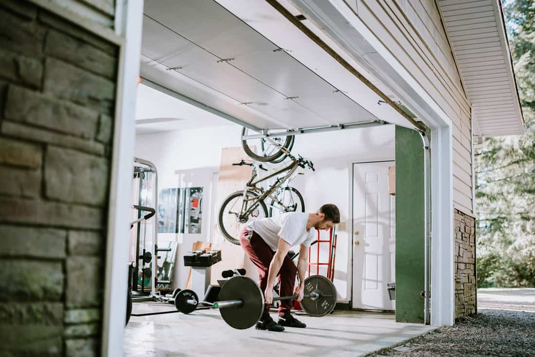A mid adult man lifts weights in his home garage. Part of a regular routine, or the new normal with social distancing and Covid-19.