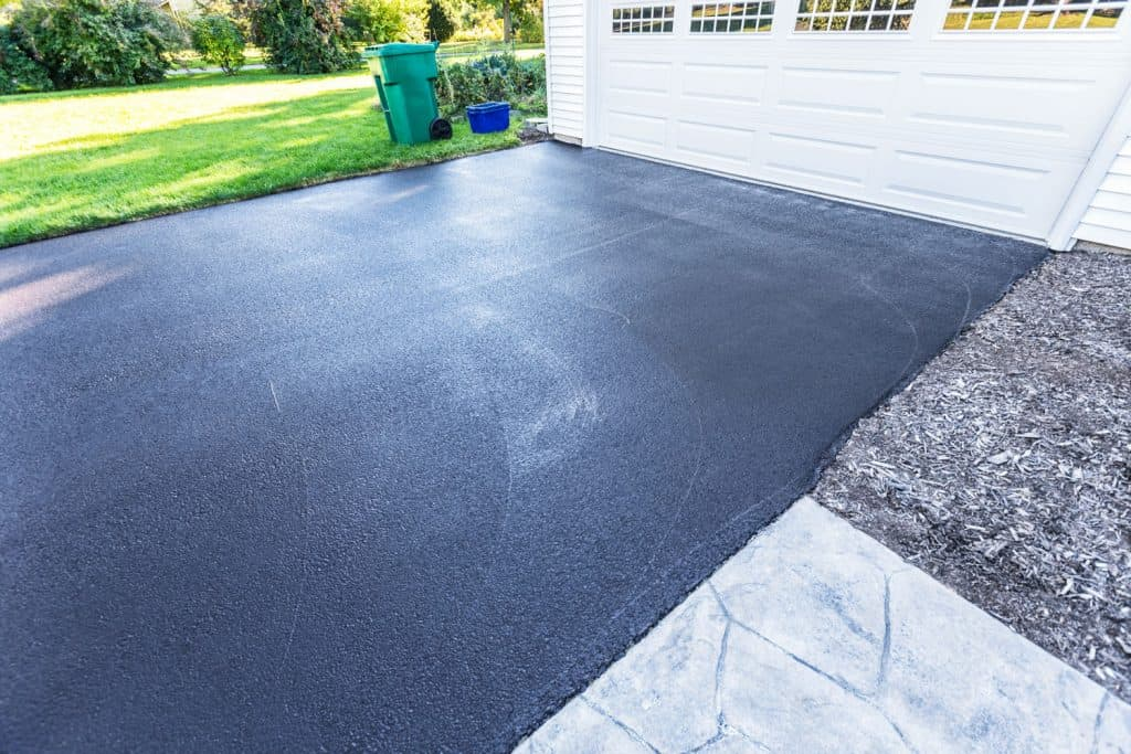 A perfectly sealed driveway with a white colored garage