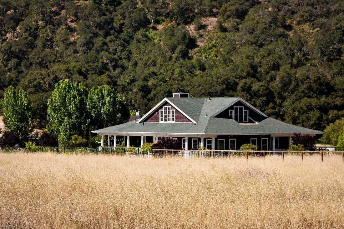 A ranch house situated on rural property with a hayfield in the foreground