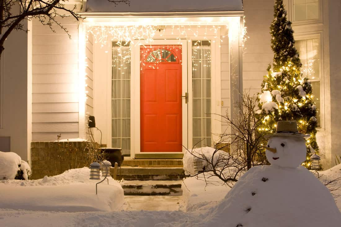 A resident house porch decorated with holiday lights at winter night