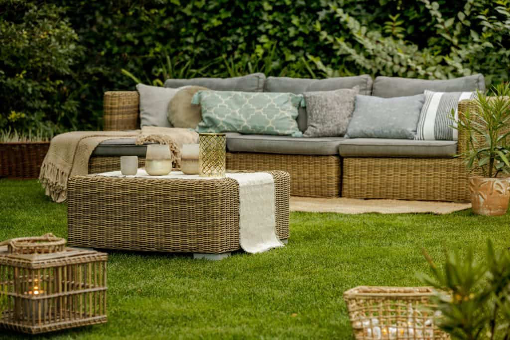 A rustic set of rattan chairs and coffee table outdoor with foams and throw pillows