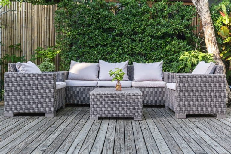 A set of Rattan chairs outdoor with throw pillows and a coffee table on the center, 4 Ways To Keep Cushions On Outdoor Furniture