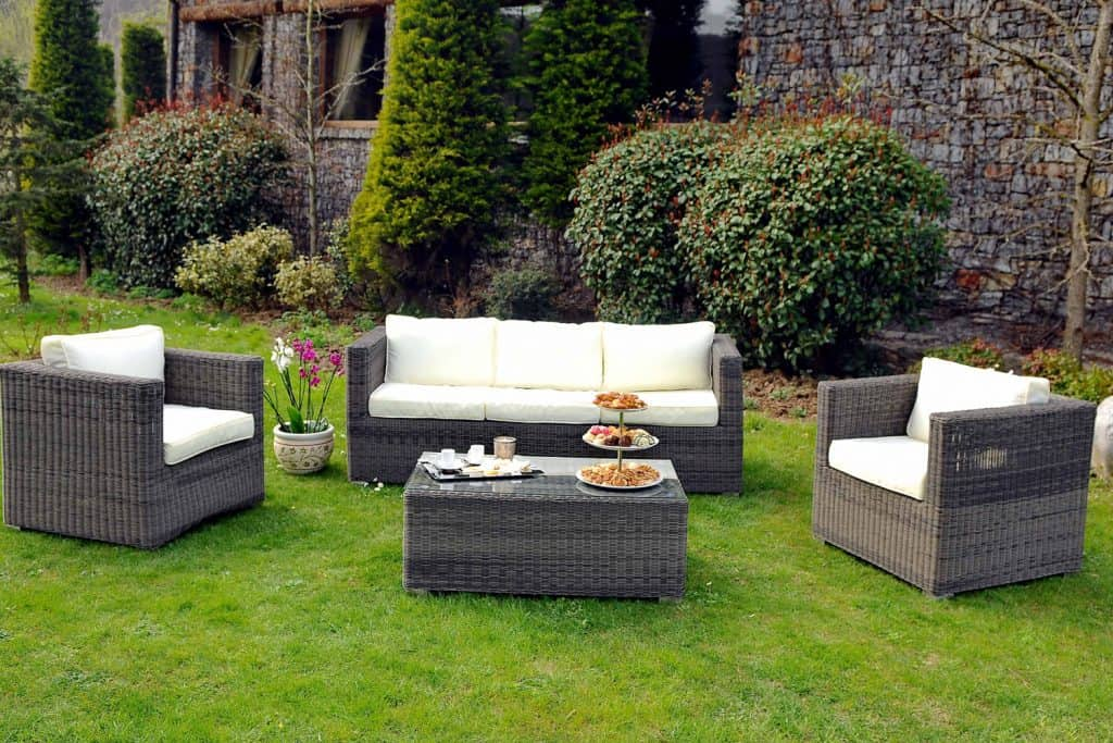 A set of rattan and wicker chairs placed outdoor with rattan coffee table on the center