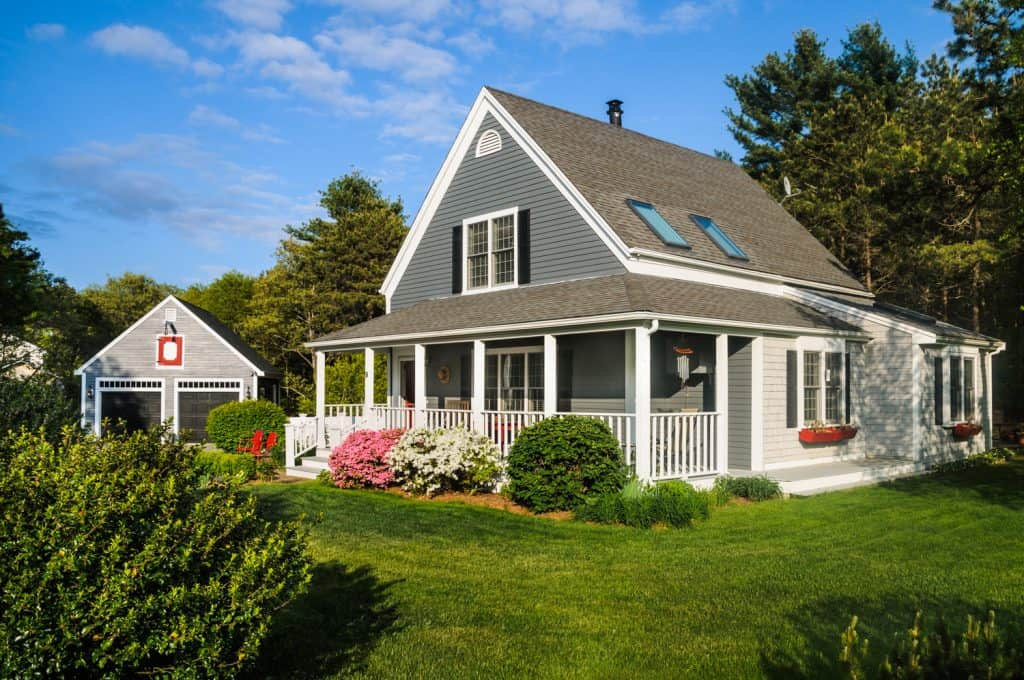 A small Cape Cod style home with a covered wrap around front porch bordered with colorful pink and white azalea bushes on Cape Cod in Massachusetts