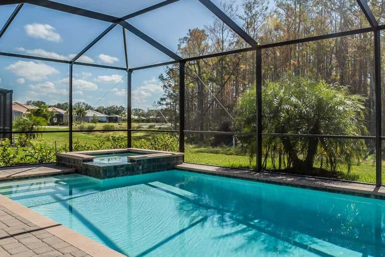 A swimming pool and net enclosure in back of home, Are Pool Enclosures Required In Florida? [A Thorough Look Into The Requirements]