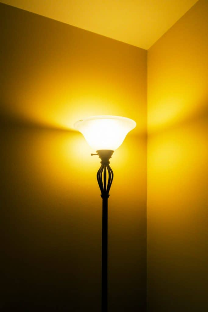A tall floor lamp glowing on the side of a room