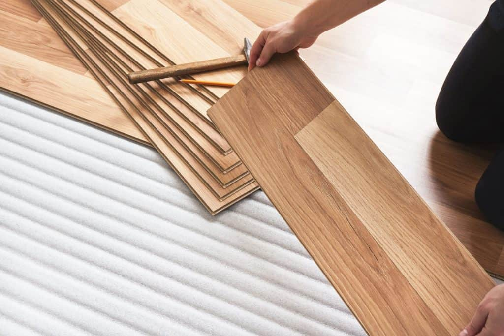 A tile setter showing a detailed photo of a laminated tiles, Which Way To Lay Laminate Flooring In A Living Room?