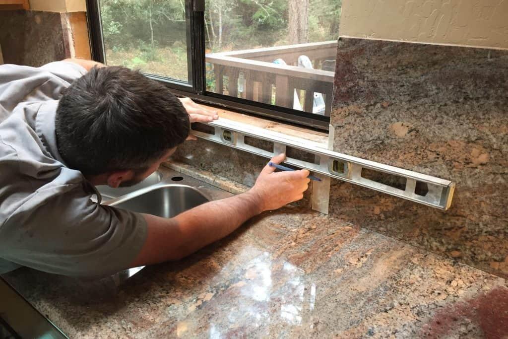 A tile setter using a level bar to align the tiles on the kitchen backsplash