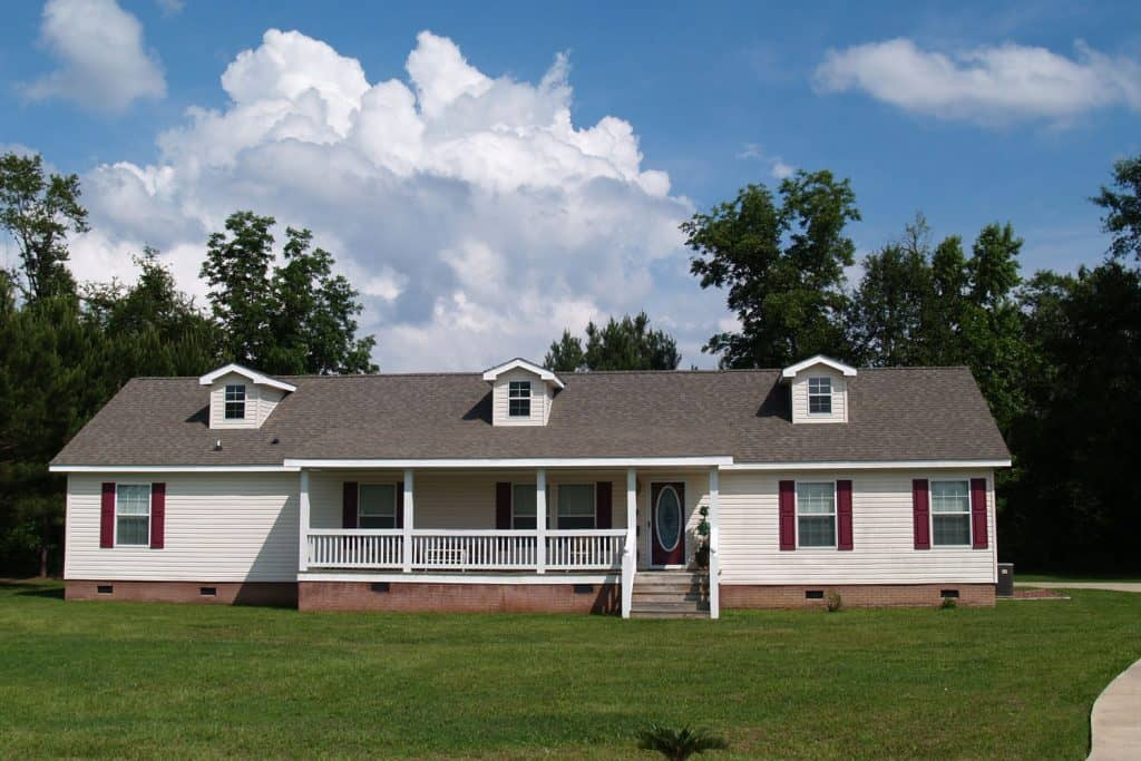 A white colored ranch style house with white painted sidings and weather asphalt shingles