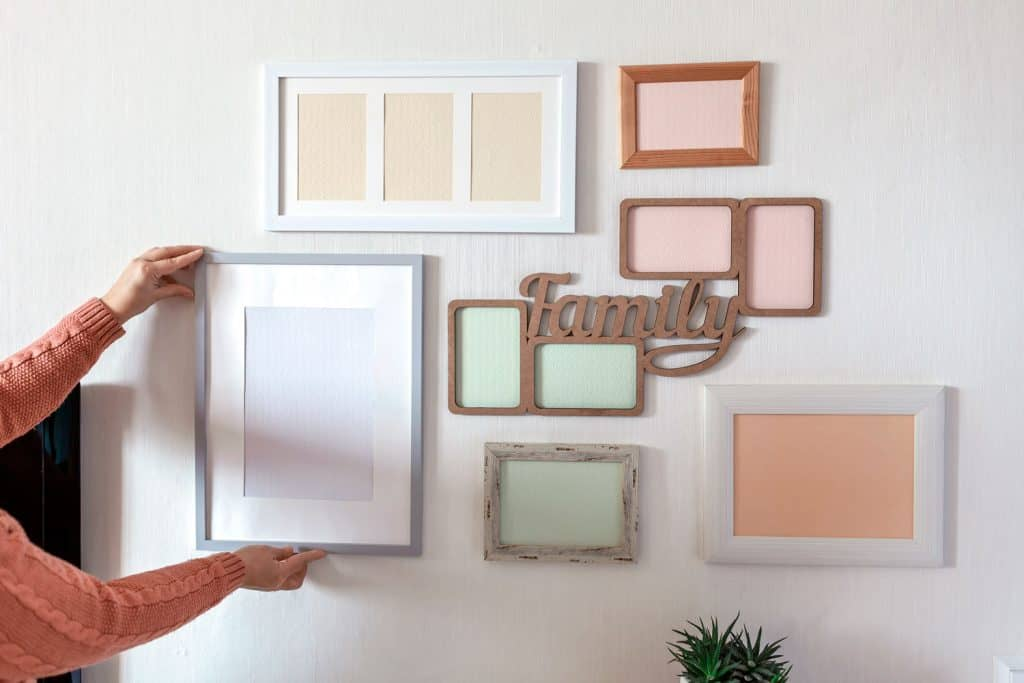 A woman putting picture frames on the wall
