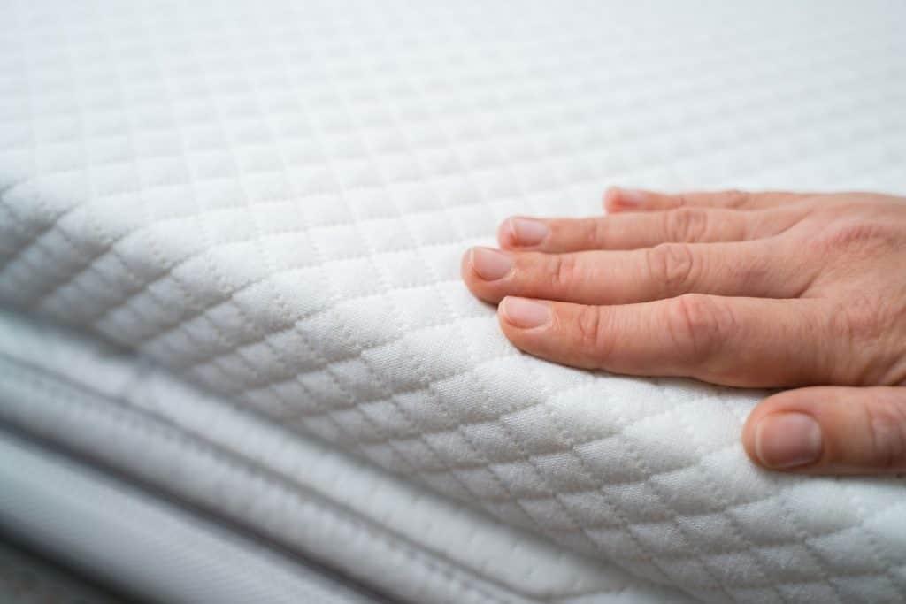 A woman touching the mattress