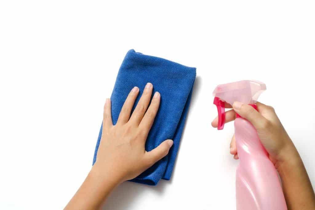 A woman using a spray and cloth to clean the bathroom