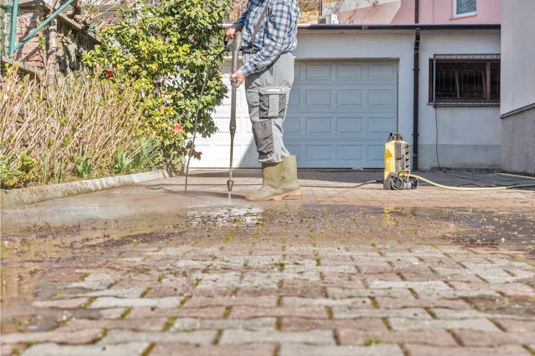 Active Senior Man Using High Pressure Washer to Clean the Entrance driveway from moss