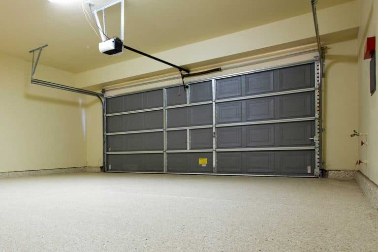 An empty garage with beige walls, Should You Paint Your Garage Floor? [And How To!]