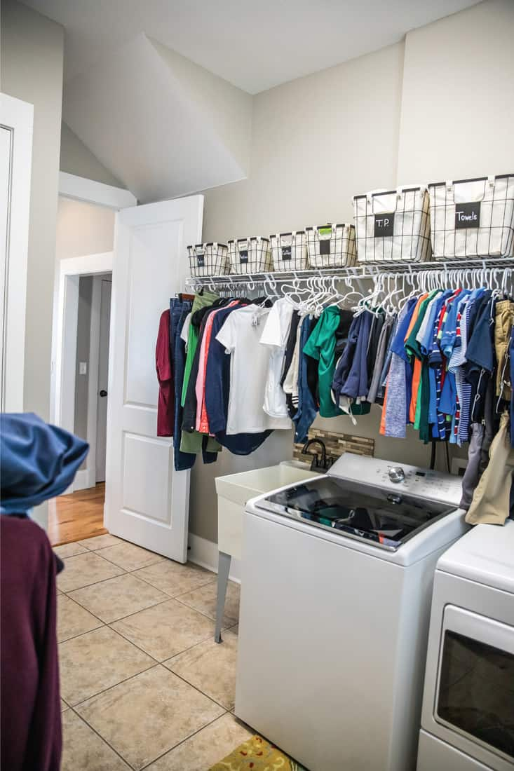 An organized laundry room with many clean shirts being hung to dry above a washer and dryer