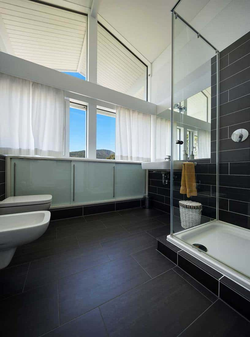 Bathroom of modern house with glass shower and high ceiling