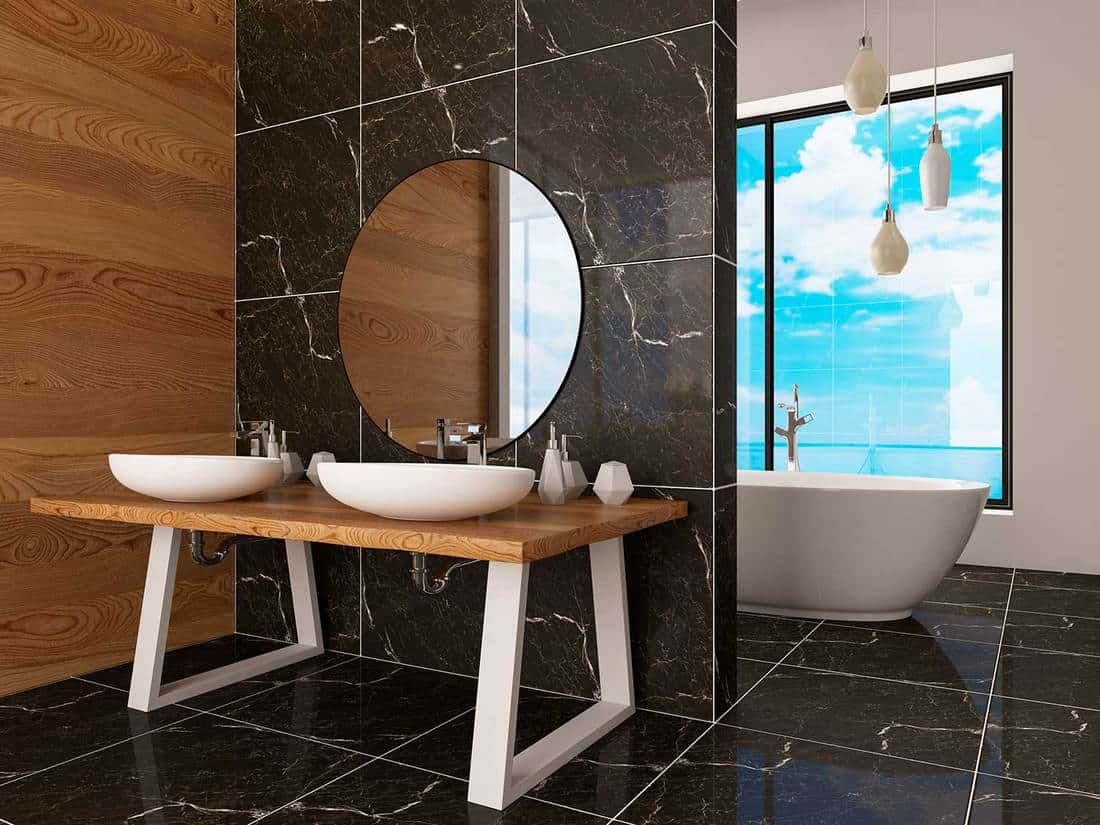 Bathtub in modern interior with dark marble tile wall and floor