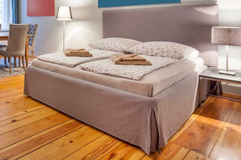 Box spring bed with a king sized mattress, blankets and pillows as well as bedside lamp, How High Is A Box Spring? [Including Various Types]