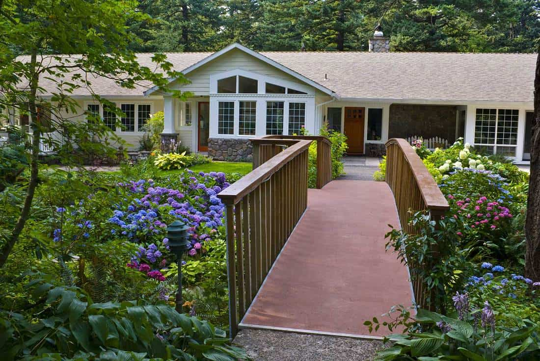 Bridge leads to ranch home surrounded by colorful gardens of hydrangeas