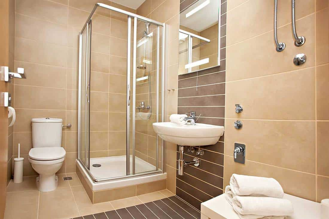 Bright new bathroom interior with glass walk in shower with cream color tile surround