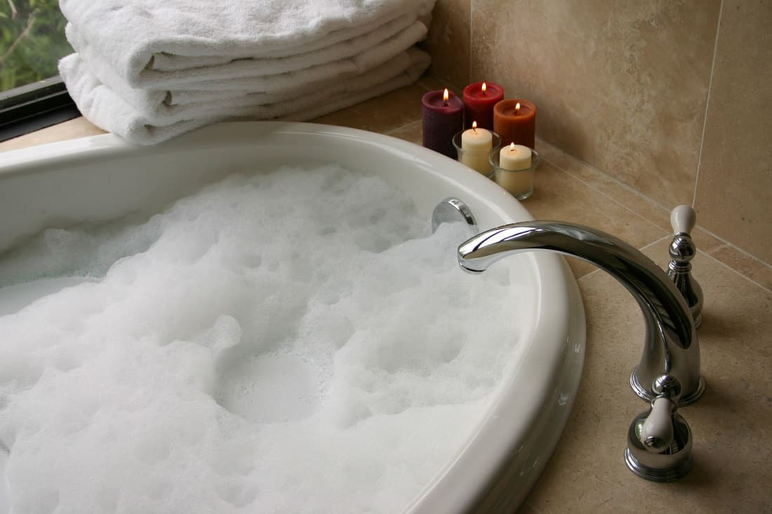 Bubble bath with candles, towels and a bathtub faucet