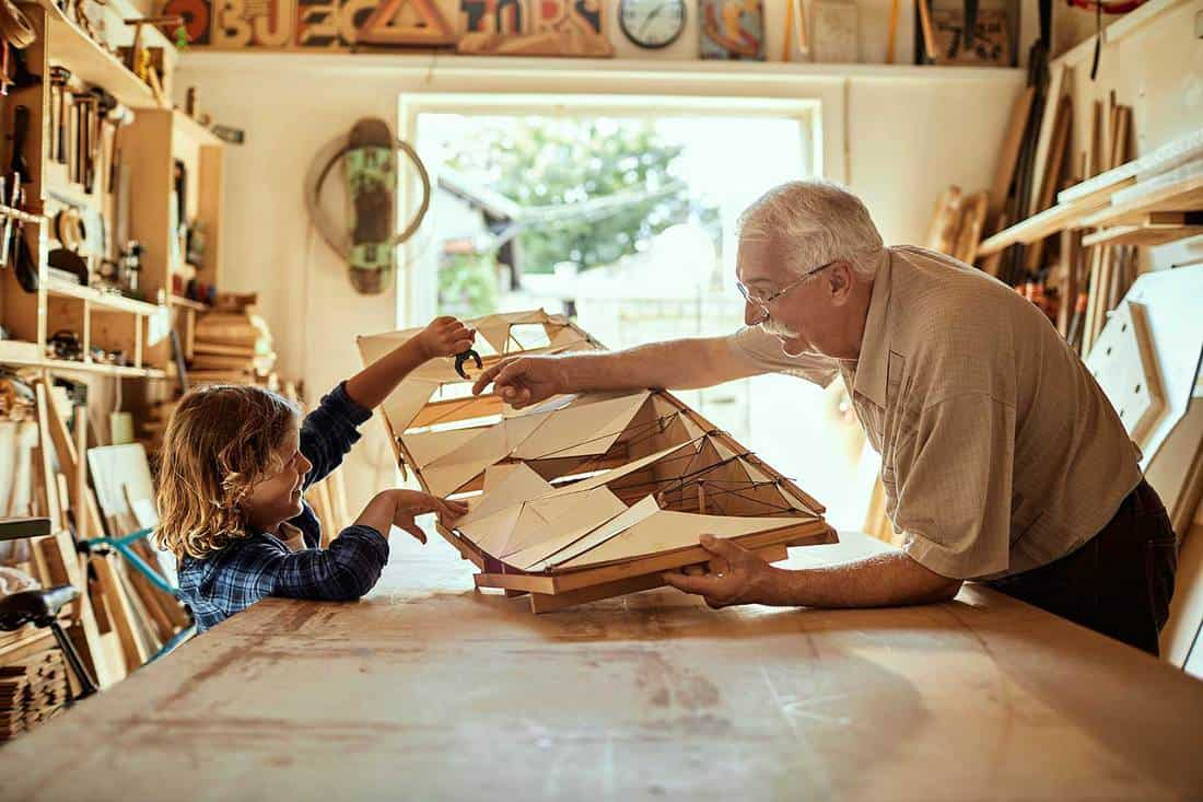 Close up of a grandfather working on a project with his grandson