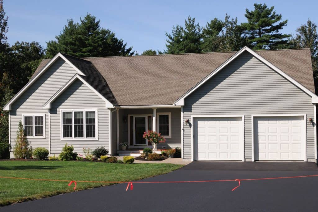 Contemporary house with gray wooden sidings, brown shingle roofing, and an asphalt driveway