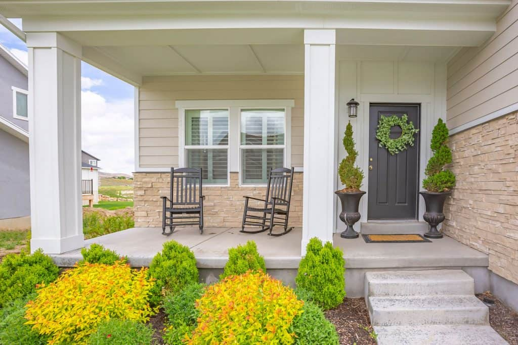 Contemporary inspired porch with decorative stone and wooden sidings