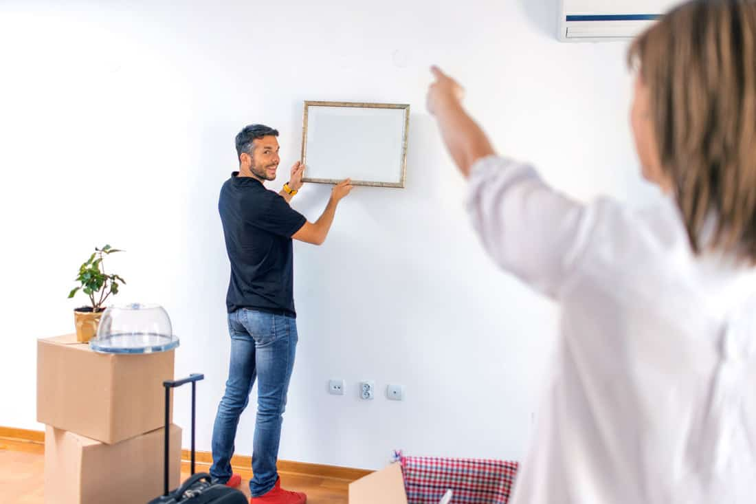 Couple hanging picture with frame on wall, 7 Tips To Hang Picture Frames Evenly