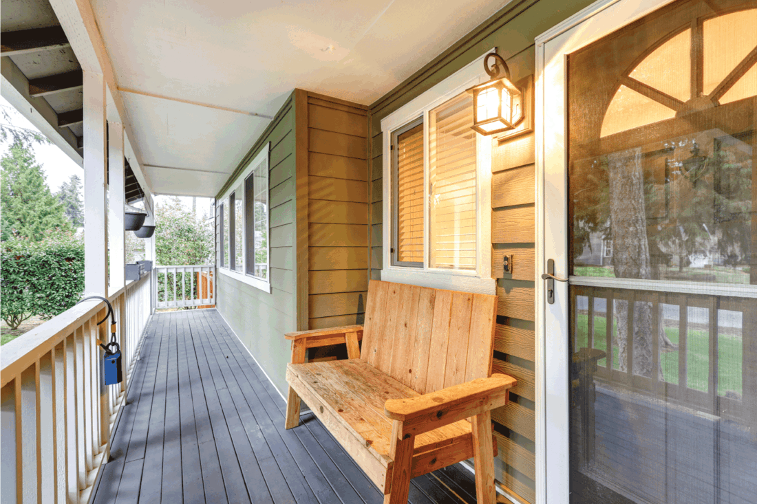 Covered front porch with rustic wood bench next to entrance door