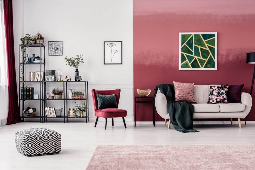 Cozy living room interior with red, ombre wall, bookcase and white sofa