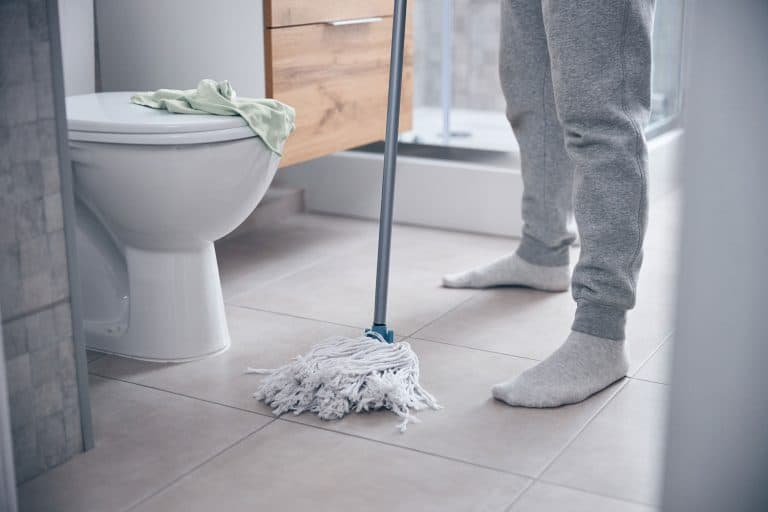 Cropped photo of a modern man standing on the floor at a ceramic toilet bowl mopped the bathroom floor, How Often Should You Mop The Bathroom Floor?