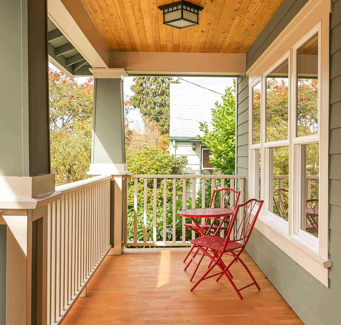 Cute and inviting front porch with red table and chairs