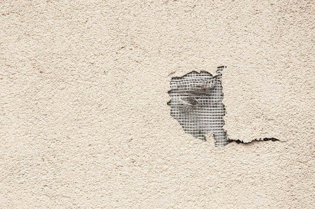 Damaged facade of the house or building with cracked plaster and hole in the exterior wall