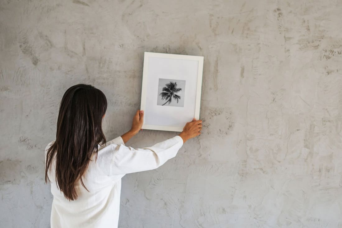 Decorating new home with a woman hanging a picture frame evenly