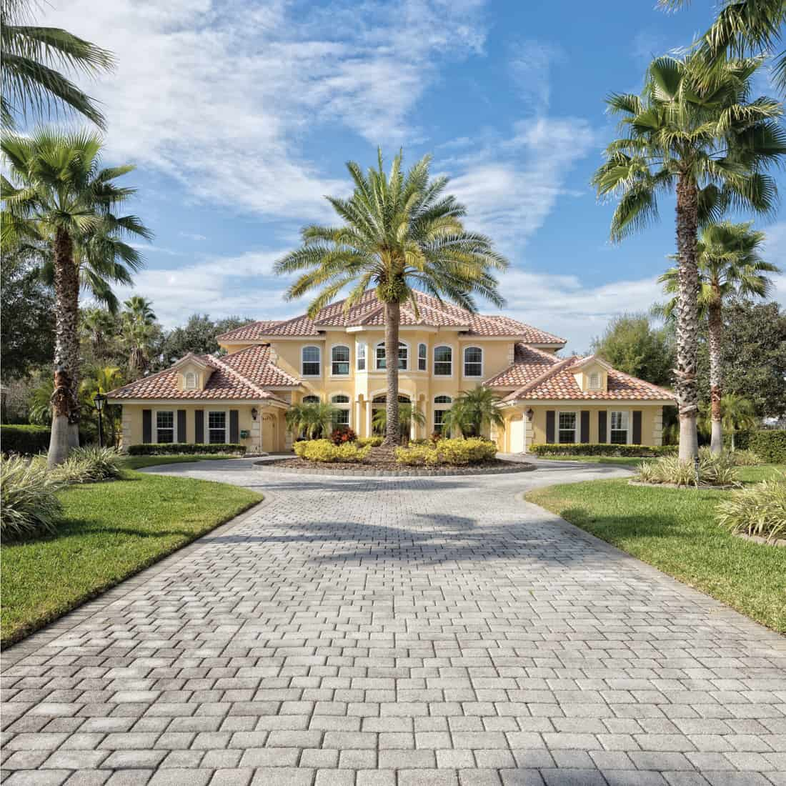 Exterior view of a beautiful estate home with paver driveway