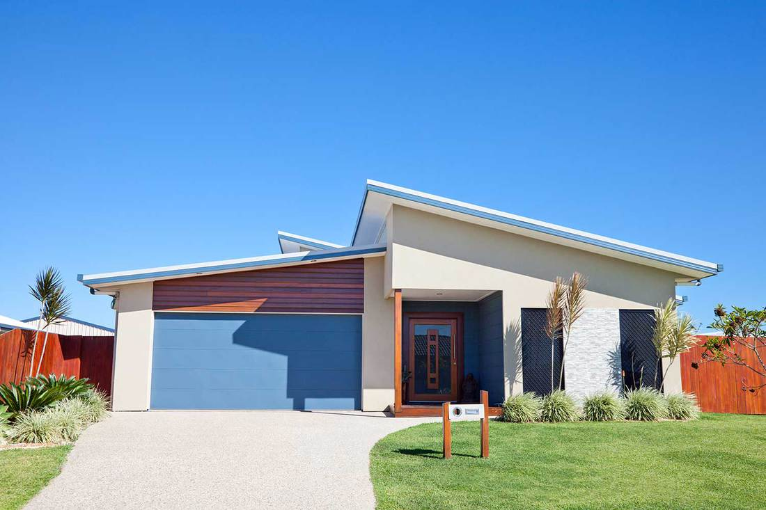 Front of a new modern family home with clear blue sky, green grass and landscaped gardens