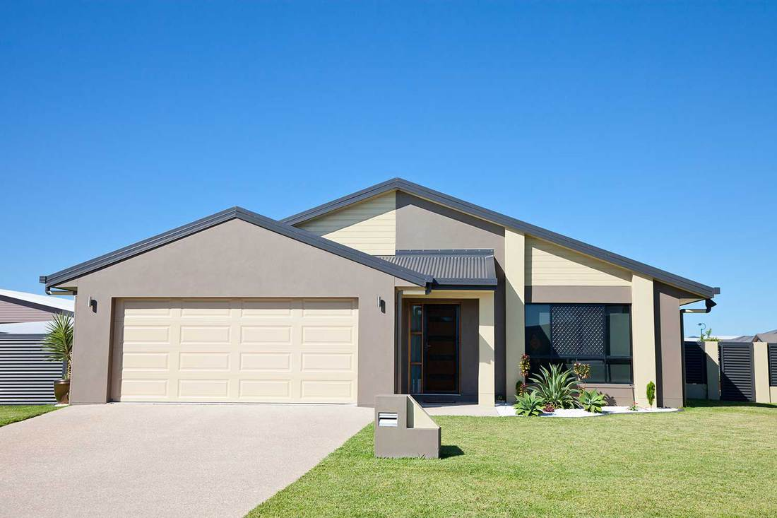 Front of a new modern single story family home with green grass and clear blue sky