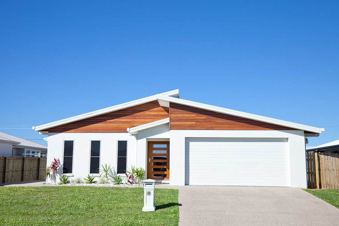 Front view of a new neat modern white low set single story family home with green grass and blue sky